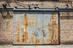 Glidning av den rostiga järnporten med tegelstenväggen för nummer ett Fotografering för Bildbyråer