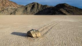 Glidning av stenar på Dry sjön i löparbanaplaya arkivbild