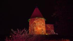 Glijdend die schot van Kaunas-kasteel bij nacht door diverse kleuren in Litouwen wordt verlicht stock footage