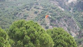 Glijscherm die boven de bomen landen stock videobeelden