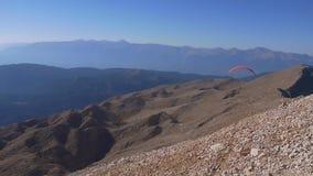 Glijscherm die onder de bergen in zonnige dag vliegen stock videobeelden