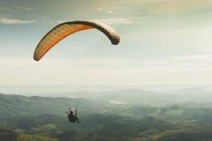 Glijscherm die op de mooie zonnige hemel over de groene bergen in Poços DE Caldas vliegen stock afbeelding