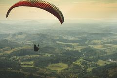 Glijscherm die op de mooie zonnige hemel over de groene bergen in Poços DE Caldas vliegen stock foto's