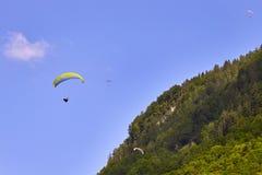 Glijscherm die over groene hellingen vliegen Zwitserse Alpen royalty-vrije stock afbeelding