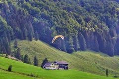 Glijscherm die over groene hellingen vliegen Zwitserse Alpen royalty-vrije stock afbeeldingen