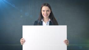 Glimlach Bedrijfsvrouwenportret met lege witte geïsoleerde raad op grijs Vrouwelijk model met lang haar Stock Fotografie
