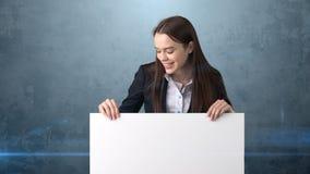 Glimlach Bedrijfsvrouwenportret met lege witte geïsoleerde raad op grijs Vrouwelijk model met lang haar Stock Foto's