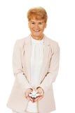 Glimlach bejaarde elegante vrouw die een stuk speelgoed vliegtuig houden Royalty-vrije Stock Fotografie