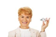 Glimlach bejaarde elegante vrouw die een stuk speelgoed vliegtuig houden Stock Foto's