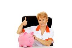 Glimlach bejaarde vrouwelijke arts of verpleegster zitting achter het bureau met piggybank Stock Foto