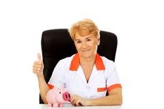 Glimlach bejaarde vrouwelijke arts of verpleegster zitting achter het bureau met piggybank Royalty-vrije Stock Afbeelding