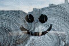 Glimlach bij het verse witte schilderen op een glasvenster dat wordt getrokken Stock Foto's