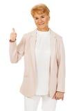 Glimlach elegante hogere vrouw die duim tonen Royalty-vrije Stock Fotografie