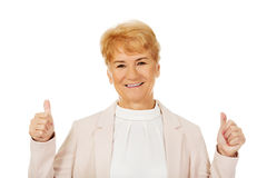 Glimlach elegante hogere vrouw die duim tonen Stock Afbeelding