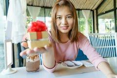 Glimlach jonge vrouw die een gouden huidige doos met rood lint geven aan Royalty-vrije Stock Foto's