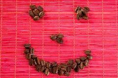 Glimlach met koffiebonen op een mat Royalty-vrije Stock Afbeeldingen