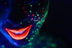 Glimlach in neonmake-up in zwart licht Royalty-vrije Stock Afbeelding