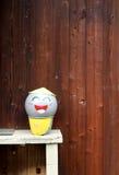 Glimlachbeeldhouwwerk en houten muur Stock Fotografie