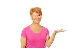 Glimlachbejaarde die iets op open palm voorstellen Royalty-vrije Stock Fotografie