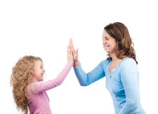 Glimlachen van de moeder en van de dochter, die hun handen slaat Stock Fotografie
