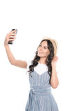 Glimlachend aantrekkelijk donkerbruin meisje in strohoed die selfie op smartphone nemen Royalty-vrije Stock Foto's