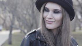 Glimlachend aantrekkelijk modieus meisje met rokerige oogschaduw die zwart hoed en leerjasje dragen actie Jonge aanbiddelijk stock footage