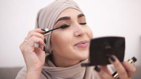 Glimlachend, aantrekkelijke moslimvrouw die make-up professioneel doen Borstelwimpers met mascara Het dragen van beige headscarf stock videobeelden