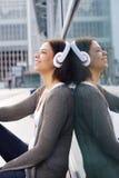 Glimlachend Afrikaans Amerikaans meisje die van muziek op hoofdtelefoons genieten stock foto's
