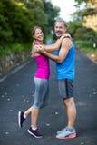 Glimlachend atletisch paar die elkaar omhelzen Stock Afbeeldingen