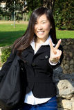 Glimlachend Aziatisch Amerikaans meisje met overwinningsteken stock foto