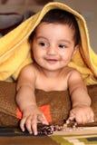 Glimlachend Aziatisch babymeisje onder gele handdoek stock afbeelding