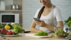 Glimlachend Aziatisch meisje die op videorecept op smartphone letten alvorens diner te koken stock videobeelden