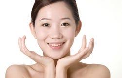 Glimlachend Aziatisch meisje met twee handen onder het gezicht Royalty-vrije Stock Foto's