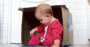 Glimlachend babymeisje binnen doos stock video