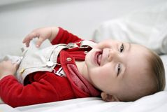 Glimlachend babymeisje dat op het bed legt stock afbeeldingen