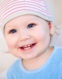 Glimlachend babymeisje dat tanden toont die een hoed dragen Royalty-vrije Stock Fotografie