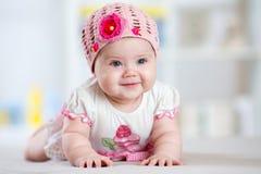 Glimlachend babymeisje die op haar buik in kinderdagverblijfruimte liggen Royalty-vrije Stock Afbeelding