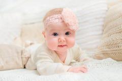 Glimlachend babymeisje met mollige wangen en grote blauwe ogen die witte kleren dragen en roze band die met bloem op bed liggen Royalty-vrije Stock Fotografie