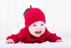 Glimlachend babymeisje op haar buik die rode appelhoed dragen Royalty-vrije Stock Fotografie