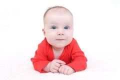 Glimlachend babymeisje in rode bodysuit op witte achtergrond Royalty-vrije Stock Foto's