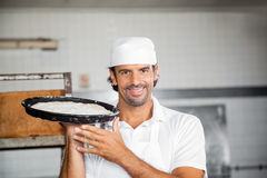 Glimlachend Baker Holding Dough Tray At Bakery Royalty-vrije Stock Foto