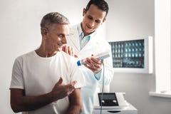 Glimlachend bejaarde die aan arts tijdens controle spreken royalty-vrije stock afbeeldingen