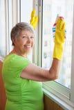 Glimlachend bejaarde die een venster schoonmaken stock afbeeldingen