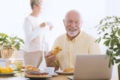 Glimlachend bejaarde die laptop met behulp van royalty-vrije stock foto's