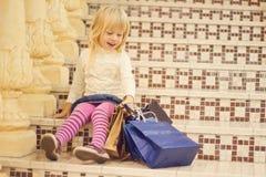 Glimlachend blond meisje 3 jaar oud met het winkelen stock foto's