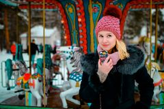 Glimlachend blond meisje in de winterkleren met mobiele telefoon in haar hand royalty-vrije stock afbeeldingen