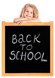 Glimlachend blond meisje die op school zwart bord leunen stock foto