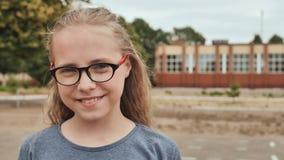 Glimlachend blonde 11 éénjarigenmeisje met glazen stock footage