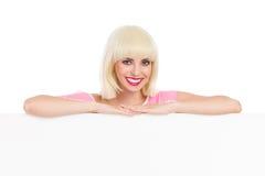 Glimlachend blonde die op een witte banner leunen Royalty-vrije Stock Afbeelding