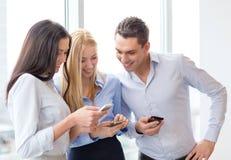 Glimlachend commercieel team met smartphones in bureau Royalty-vrije Stock Foto